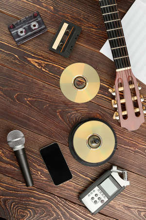 Vintage musical devices on wooden background. Top view on compact discs, audio cassettes, acoustic guitar, microphone, music sheets, voice recorder and smartphone.