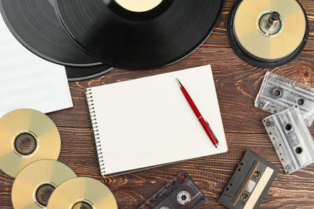 Retro audio devices and blank notebook. Work space with vinyl records, compact discs, analogue cassettes, musical notes, paper notepad and pen. Vintage audio storage.