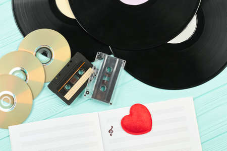 Compact discs, cassettes and vinyl records. Outdated musical devices background. Love music concept.