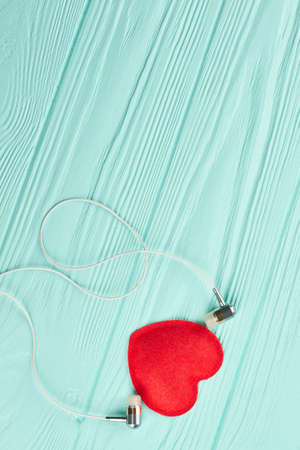 Earphones and red heart on wooden background. Red heart and headphones on blue background with copy space, top view. Love listening music.