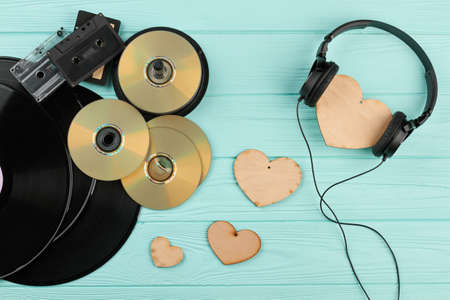 Vintage musical devices and wooden hearts. Vinyl records, dvd discs, audio cassettes, headphones and heart-shaped decorations. Love music concept.