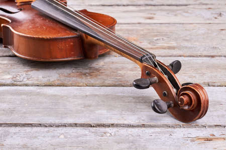 Violin on old wood, cropped image. Violin scroll and peg box. Classical orchestral instrument.