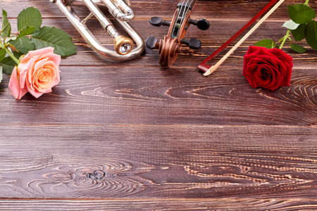 Musical instruments and roses on wooden background. Trumpet, violin, fiddle stick, roses and copy space. Music still life.