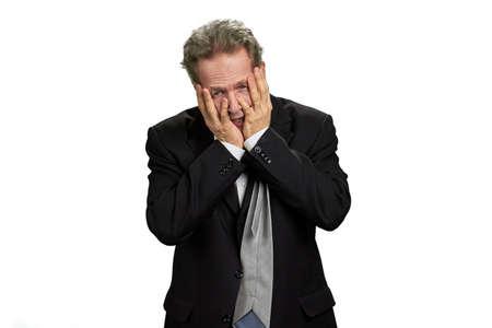 Depressiver Mann bedeckt sein Gesicht mit den Händen. Hoffnungsloser depressiver Geschäftsmann im schwarzen Anzug isoliert auf weißem Hintergrund.
