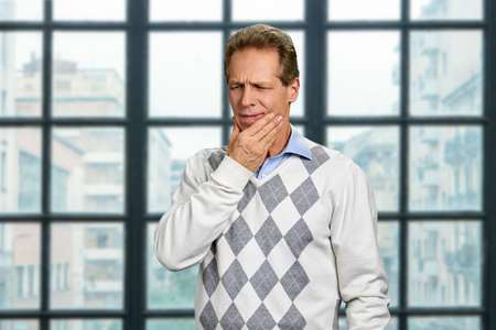Mature man suffering from toothache. Middle-aged office worker touching his cheek because of terrible toothache on office window background.