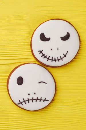 Halloween gingerbread cookies on yellow background. Jack Skellington sugar cookies. White Halloween cookies on color background.
