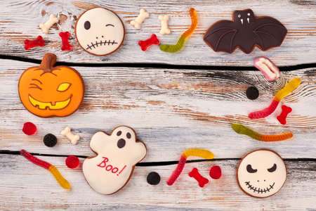 Frame from Halloween sweets with copy space. Halloween cookies and candies on vintage wooden background. Halloween holiday greeting card.