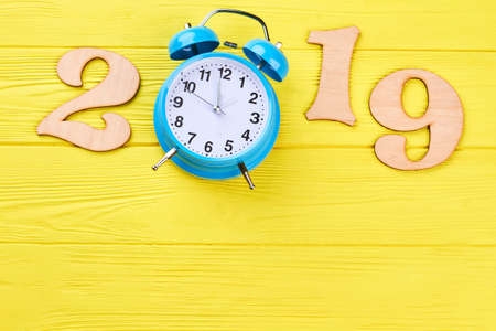 Number 2019 from wood and alarm clock. New year 2019, clock count down, yellow wooden background, copy space. Happy New Year. New Year 2019 concept. 스톡 콘텐츠