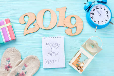 Happy New Year 2019 wooden background. Cut out wooden text 2019, alarm clock, knitted handmade mittens, gift box, candle lantern, paper notebook with text Happy New Year, top view. 免版税图像