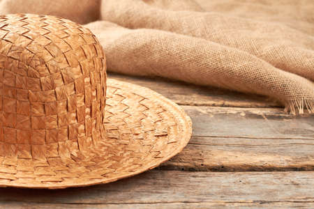 Straw hat on rustic wooden background. Natural wicker hat and hessian fabric cloth on wooden planks. Reklamní fotografie