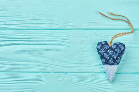 Handmade textile heart and copy space. Blue fabric heart on colored wooden background. Valentines Day accessory.