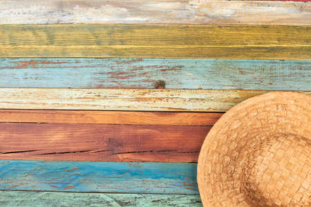 Brown handmade hat o colorful background. Straw panama on old weathered table with copy space. Summer beach accessory.