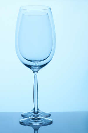 Two empty wine glasses standing together. Blue lighting. Imagens
