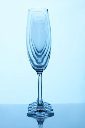 Glass champagne cups in a row. Side view. Visual effect, light deformation.