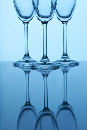 Long stem champagne flutes. Reflective surface, blue lighting. Imagens