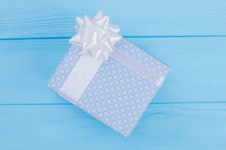 Ornamented gift box with white ribbon. Blue wooden background.