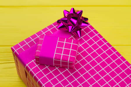 Big and small gift boxes on color background. Pink present boxes on yellow background. Christmas, Birthday or Valentines Day.