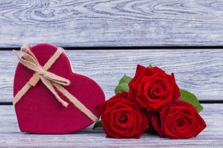 Red roses and heart-shaped gift box. Romantic background with flowers and gift. Happy Valentines Day.