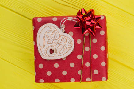Ged dotted gift box and heart shaped wood. Decorative handmade wood with I love you heart. Yellow wood background.