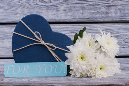 Romantic background with flowers and gift box. Valentines Day background with present box in a shape of heart and beautiful chrysanthemums on wooden table. Stok Fotoğraf