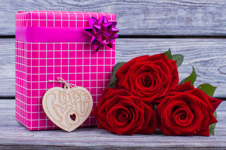Flowers and gift box on wooden background. Flowers, wooden heart and present box. Valentine holiday concept. Foto de archivo