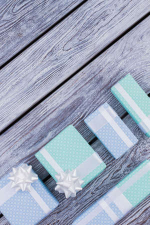 Holiday presents on wooden background. Wrapped in blue and turquoise paper gifts for Christmas, Birthday or other celebrations, top view. Stock Photo