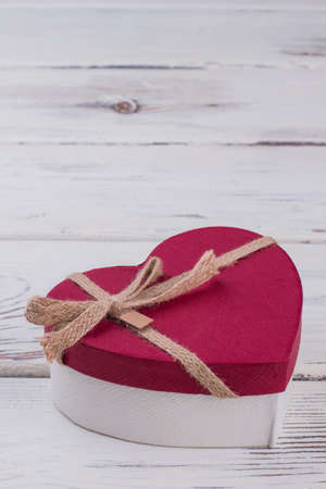 Valentines Day gift box on wooden background. Red heart-shaped present box tied with ribbon and bow. Love holiday greeting card. 版權商用圖片