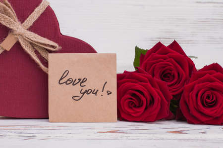 Valentines Day background. Red roses, heart-shaped gift box and written inscription love you close up. Stock Photo