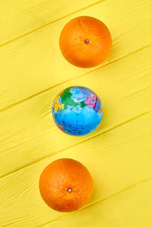 Fresh oranges and small round globe on yellow wooden background, top view.