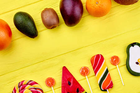 Yellow wooden background with assortment of fresh organic fruits and lollipops with copy space. 写真素材