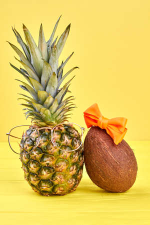 Pineapple in eyeglasses and coconut with red bow on yellow background. Imagens