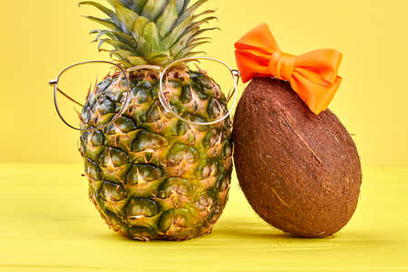 Hawaiian pineapple in eyeglasses and cococut with hairbow on yellow background.