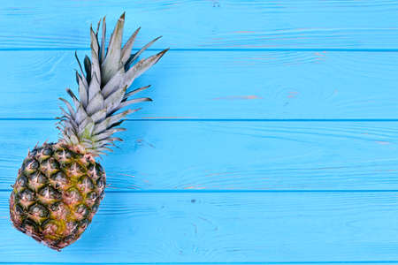 Whole hawaiian pineapple fruit on blue wooden table with text space. Stock Photo
