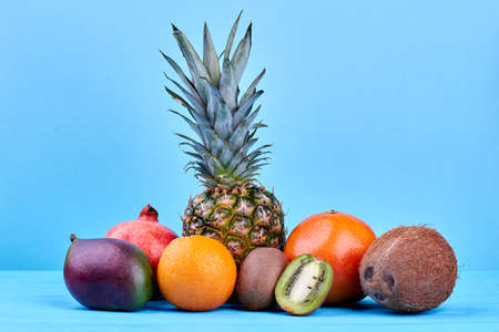Composition of fresh tropical fruits. Assortment of ripe exotic fruits on blue background. Imagens