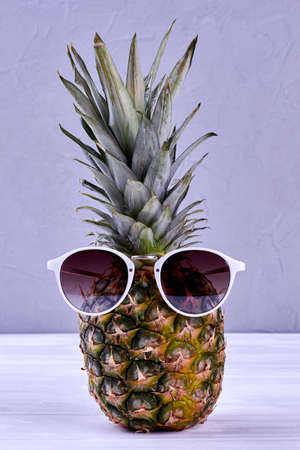e01fe11d818c Hipster pineapple with sunglasses against a grey background. Stock Photo