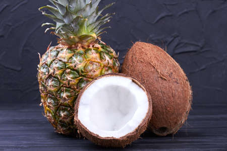 Fresh pineapple and coconuts on dark background.