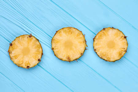 Round slices of fresh pineapple on blue wooden background. Imagens