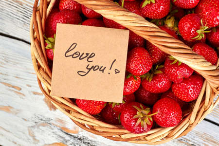 Red healthy strawberries in basket. Handwritten text love you. Фото со стока