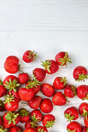Ripe juicy strawberries scattered on white wooden surface.