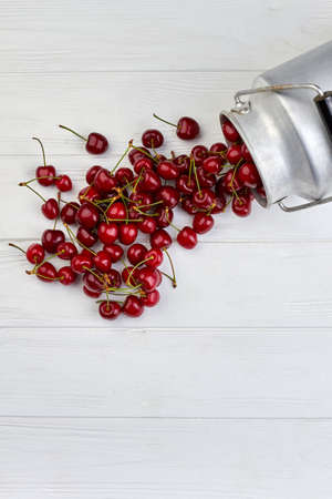 Ripe delicious berries spilled out from aluminium container.