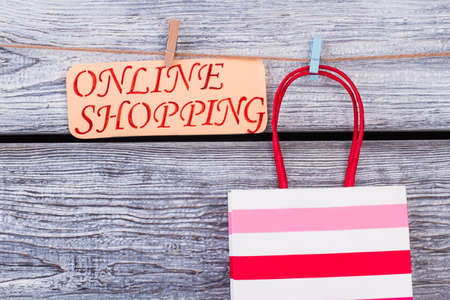 Striped shopping bag on wooden background. Gift bag and card with inscription online shopping. E-business and e-commerce. Stok Fotoğraf