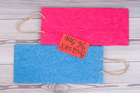 Flat lay shopping bags on wooden background. Two colored paper bags and red card with inscription big saving. Shopping offer concept.