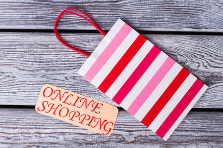 Striped shopping bag with red handles. Laminated gift bag and card with inscription online shopping.