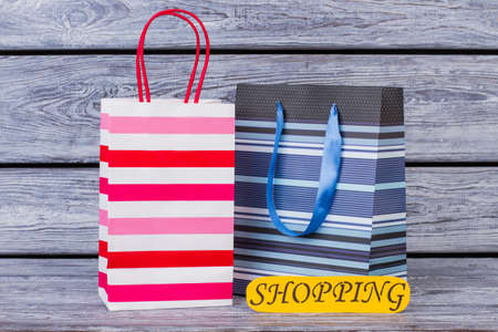 Shopping bags on wooden background. Paper shopping packets and color card with inscription shopping. Holiday sales concept. Stock Photo