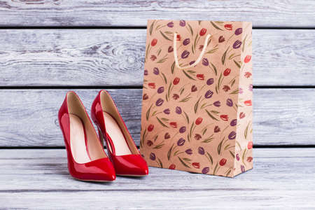 Red lacquered heels and shopping bag. Female leather stilettos and paper bag with spring tulip pattern. Female spring purchase. Stock fotó