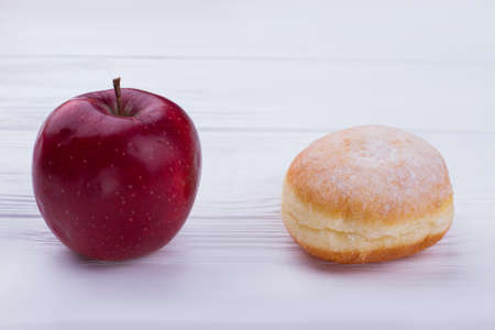 Tasty donut and fresh red apple. Cream doughnut and fresh fruit. Healthy eating concept. Stock Photo