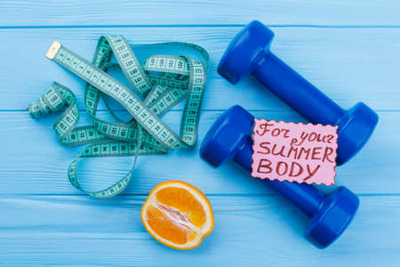 Sport lifestyle and weight loss concept. Measuring tape, dumbbells, orange fruit and card with incription for your summer body. Get fit concept.