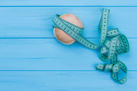 Donut and measuring tape on wooden background. Doughnut wrapped in measuring tape, copy space. Diet time concept. Stock Photo