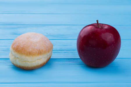 Donut and red apple on wooden background. Junk food and healthy food: make your choice. Dieting and health care concept. Stock Photo