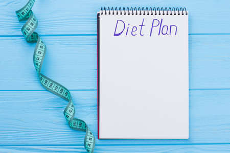 Diet plan concept. Measuring tape and paper notebook with inscription diet plan on blue wooden background. Healthy slimming diet and fitness concept. Imagens